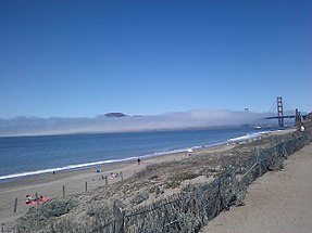Baker Beach With Fog Rolling Across The Golden Gate Strait And Bridge