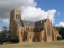 Exterior of Goulburn Cathedral. Built in honey-coloured stone, it has very large ornately-traceried windows in both the chancel and the transepts. Paired clerestory windows rise above the side aisles. The terminals of the gables have tall pinnacles. The tower which rises behind the chancel is square at the top.
