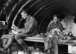 Two men in military uniform in a building. The man on the left has something in his mouth and is sitting down looking at some papers, angled away from the camera. The men on the right is smiling and looking at the camera. The roof of the structure is curved.