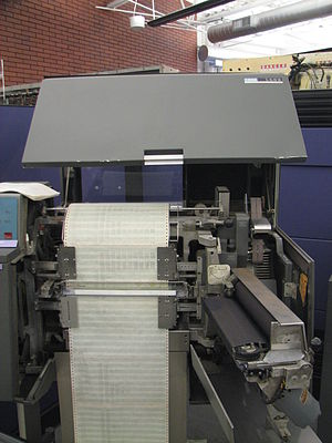 IBM 1403 - IBM 1403 printer opened up as it would be to change paper. The print chain is behind the wide black ribbon, hinged open to the right, which is the width of the paper. Also note carriage control tape in upper right.