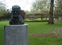 "Bronze bust of Joyce in a green park. The bust is poorly lit and only the forehead can be made out clearly. The bust is atop a pedestal saying ""JAMES JOYCE 1882–1941""."