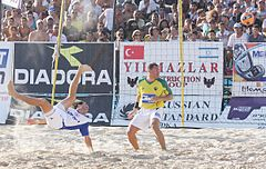 Photograph of two men in a beach soccer pitch