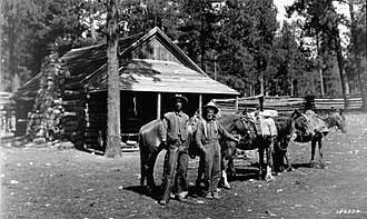 """Jacob Lake, Arizona - """"Uncle"""" Jim Owen (right) and his pack train at Jacob Lake, 1918. Owen, a famous guide and hunter, was known as the """"Cougar killer"""" of the Kaibab."""