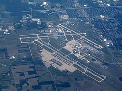 Aerial image of Dayton International Airport showing runways, taxiways, buildings, and surrounding area.