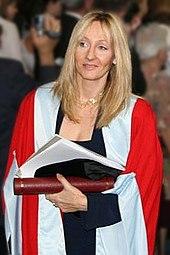 Une femme blonde porte une cape fine rouge et blanche et tient contre elle dans sa main un tube rouge et plusieurs documents.