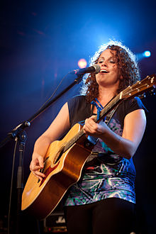 A photograph of a woman with shoulder-length, curly, brown hair playing a guitar with a pick and singing into a microphone, backlit with a blue light
