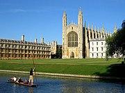 مبنى حجري أصفر ذو نافذة مقوسة وبرجان في آخر الصورة. يمكن رؤية العشب والماء في مقدمة الصورة مع أشخاص قابعين في قارب البنط.