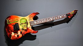 Wall-mounted electric guitar on display in a museum