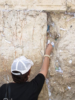 Placing notes in the Western Wall - A woman places a prayer note in the Wall.