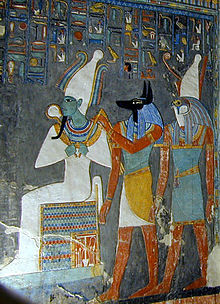 Painted relief of a seated man with green skin and tight garments, a man with the head head of a jackal, and a man with the head of a falcon