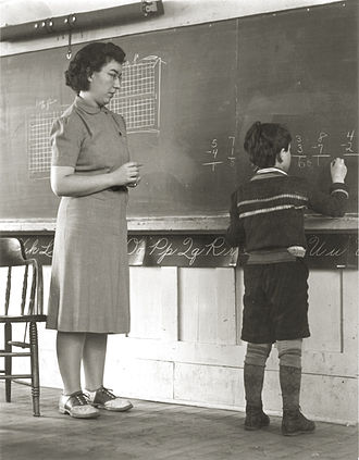 Landaff, New Hampshire - A new Landaff teacher in the 1940s watches as a student writes on the blackboard.