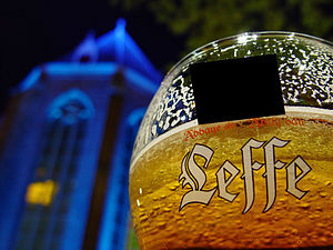 Glass of Leffe Blonde, a Belgian beer, in fron...