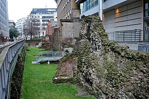 Photograph of ruins of the London Wall between a street and office buildings.