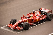 en röd racerbil med öppet hjul färdas med hastighet på en asfalterad bana