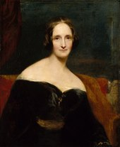 Half-length painted portrait of a woman wearing a black dress, sitting on a red sofa. Her dress is off the shoulder, exposing her shoulders. The brush strokes are broad.