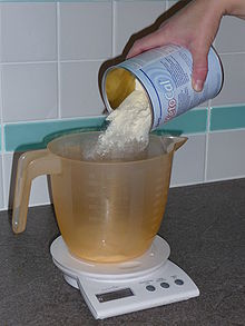 A cream-coloured powder is poured from a tin into a measuring jug on an electronic kitchen scale.