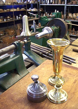 "Metal spinning - A brass vase spun by hand. Mounted to the lathe spindle is the mandrel for the body of the vase; a shell sits on the ""T"" rest. The foreground shows the mandrel for the base. Behind the finished vase are the spinning tools used to shape the metal."
