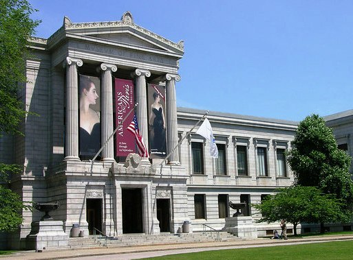 Gray stone classical building with columns and art banners on the central façade