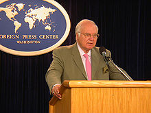 "A white-haired man in a suit and pink tie is standing at a lectern, speaking into a microphone. Behind him is a plaque reading ""FOREIGN PRESS CENTER WASHINGTON""."