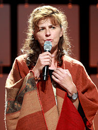 A photograph of Mira Furlan, a woman who is about 60 years old and has brown hair. She is wearing a red shawl and is singing in this image.