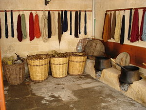 Natural dye - A dye-works with baskets of dyestuffs, skeins of dyed yarn, and heated vats for dyeing.