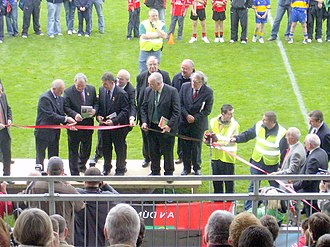 Nickey Brennan - Brennan (second from left) cuts the ribbon at the official re-opening of Páirc Esler in Newry