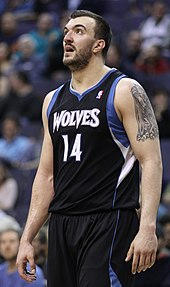 Nikola Peković, bearded, in a black Timberwolves jersey with blue and white trim