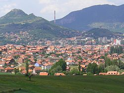 View o the Kosovska Mitrovica, wi North Kosovska Mitrovica in the backgrund, Zvečan Fortress on the muntain tae the left, an Trepča chimney on the richt.