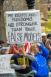 "Ohio protestor with sign saying, ""My rights and freedoms are stronger than your false model"""