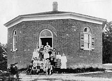 A black-and-white photo of students and their teacher in front of the Eight Square Schoolhouse, an eight-sided one-room schoolhouse, in Dryden, New York, in 1890