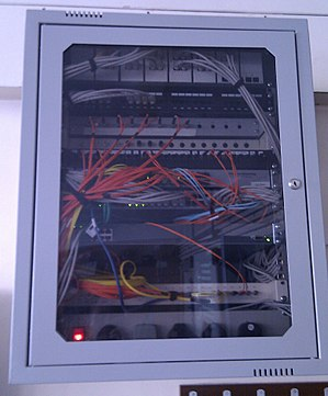 Optical fiber - A wall-mount cabinet containing optical fiber interconnects. The yellow cables are single mode fibers; the orange and aqua cables are multi-mode fibers: 50/125 µm OM2 and 50/125 µm OM3 fibers respectively.