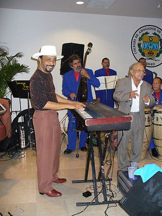 La Sonora Ponceña - Papo Lucca, playing piano with the Sonora Ponceña; his father Quique Lucca stands next to him