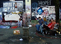 Photograph of people, graffiti-covered walls, and litter in Pigeon Park