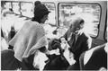 Photograph of President Gerald R. Ford Talking to a Woman Refugee while Holding a Vietnamese Baby on a United States... - NARA - 186795.tif