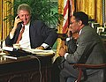 Photograph of President William J. Clinton and Secretary of Agriculture Mike Espy on Telephones in the Oval Office (croppeda).jpg