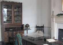 Photography of a library, showing a hutch with books in it and a table with various items on it.
