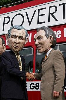 Photographie couleur de deux personnes qui portent les masques de George W. Bush et Tony Blair et se sèrent la main.