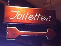 "Bathroom sign in French restaurant in USA, spelling ""Toilets"" to convey a French aura, but understood by monolingual English speakers."