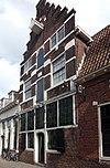 foto van Huis met trapgevel met hardstenen banden en blokken in bogen boven de ramen. Deels pakhuis