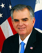 Older man in front of a US flag with bushy eyebrows and gray hair in a suit with a blue tie
