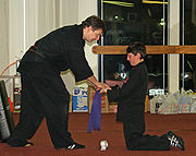 A young student graduates up a rank in belt in front of his dojo.