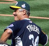"An older white male wearing a green cap with a yellow bill, a blue jersey, with the lettering ""FINGERS"" and a number 34 below it on the back, on a grass field."