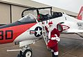Santa Claus and an elf get out of a T-45C Goshawk for a Christmas party. (31437005585).jpg