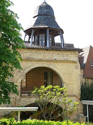 Vue partielle, en fond de jardin, d'un bâtiment avec loggias à arcade au rez-de-chaussée et à l'étage. Il est coiffé d'un lanterneau octogonal.
