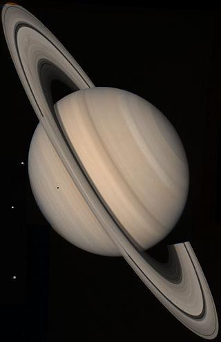 Cette photo couleur est un assemblage de clichés de Voyager 2 depuis une distance de 21 millions de km. Trois satellites de Saturne sont visibles à gauche; de haut en bas: Téthys (1050 km de diamètre), Dioné (1120 km), et Rhéa (1530 km). L'ombre de Téthys forme un point noir sur la planète.