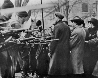 Bread and Roses Strike. Massachusetts National Guard troops surround unarmed strikers in Lawrence, Massachusetts, 1912. Standoff between militia and strikers, Lawrence, Mass.png