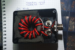 Balun - Picture a 4:1 balun of the same design, wound on ferrite toroid. Notice that the black and red winding wires are joined at the threaded connector.