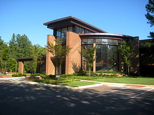 A tan brick building with dark glass walls, including a large curved glass wall facing the viewer. In front of the building are trees and a lawn, and in front of that a driveway and parking spaces.