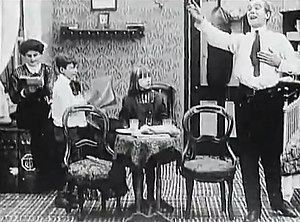 Thanhouser Company - A still from The Actor's Children. It shows the family with the father doing some theatrical acting for the amusement of his children.
