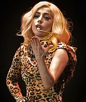 A woman blowing a kiss while wearing a leopard print outfit.